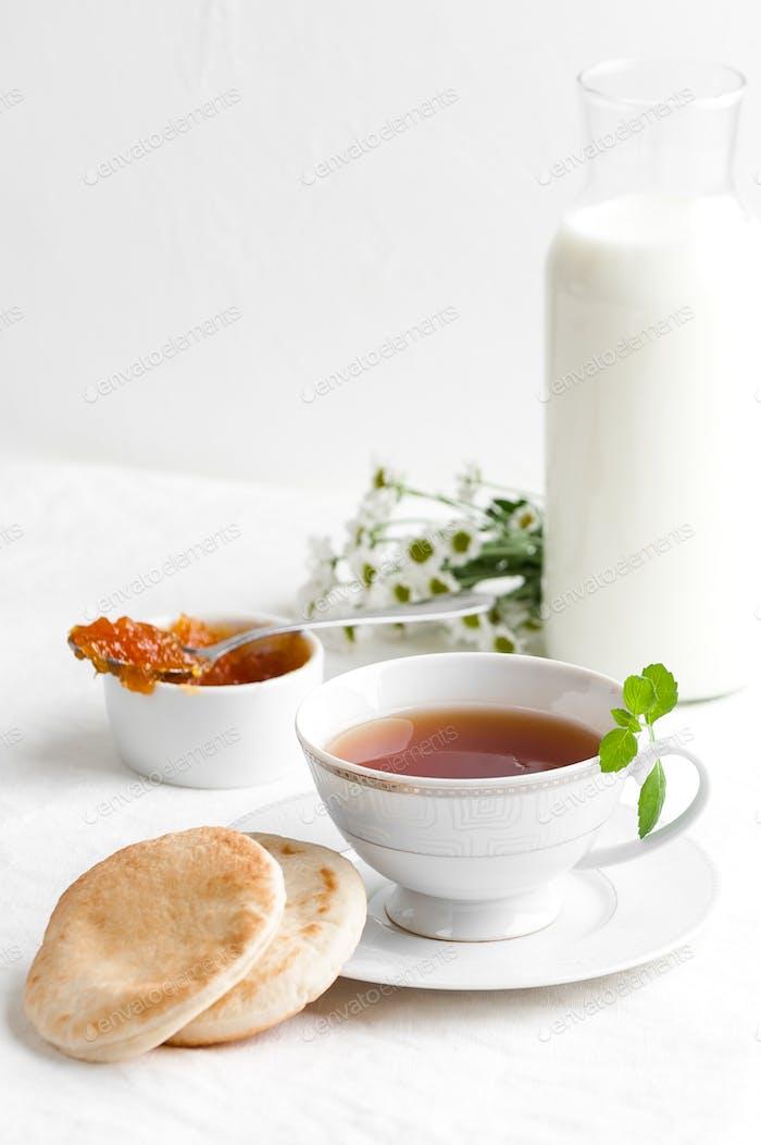 Eine Tasse schwarzen Tee, Marmelade und eine Flasche Milch.
