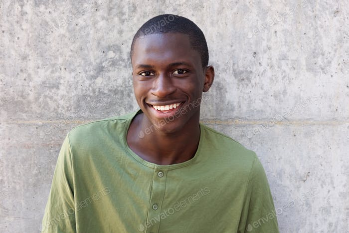 Cheerful young african man standing against wall