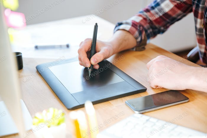 Black pen tablet with stylus used by male designer hand