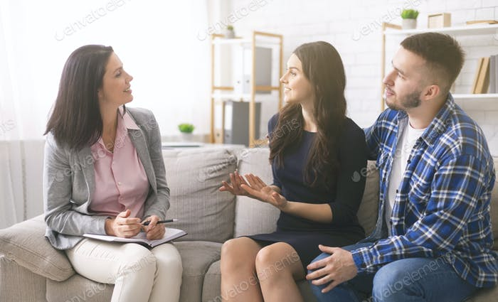 Cheerful young spouses talking to professional marital counselor