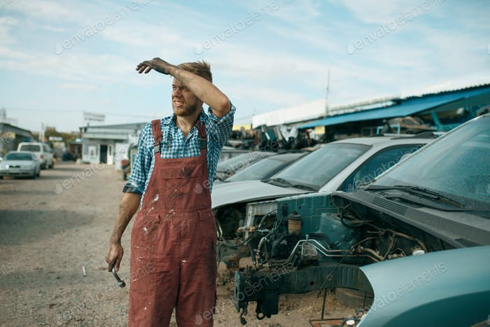 Tired repairman with wrench on car junkyard