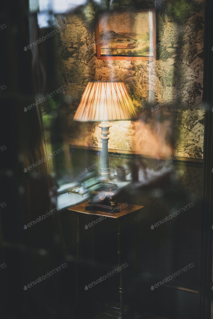 View through curtain of blue vintage table lamp with cream pleated lampshade.
