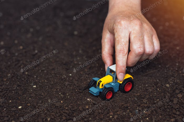 Farmer playing with small agricultural tractor toy
