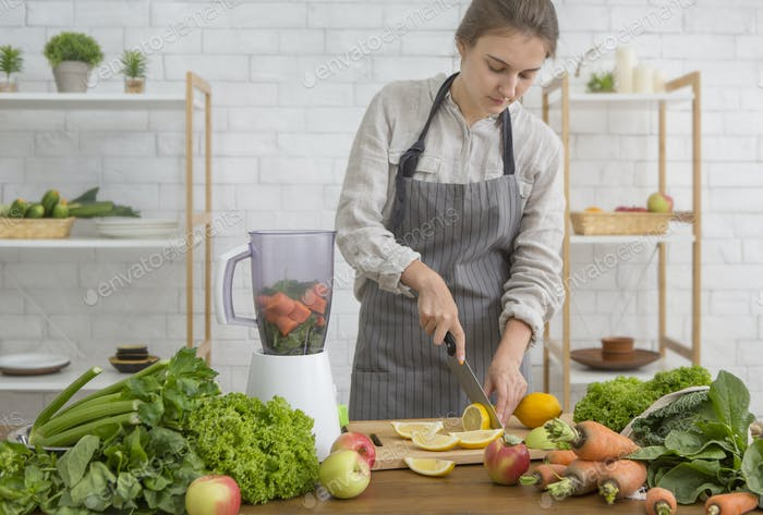Young woman preparing vegan smoothie with greens, citrus