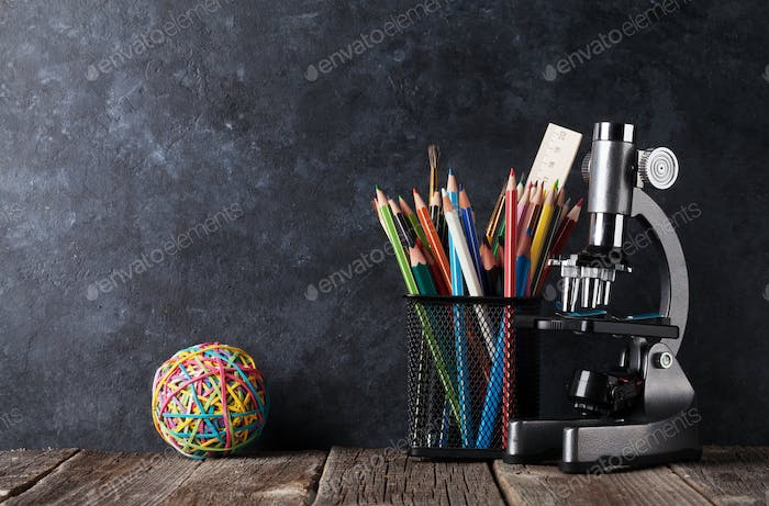 Supplies and microscope in front of chalk board
