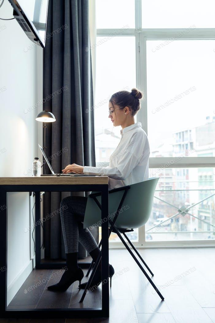 Concentrado hermosa mujer de negocios trabajando con su computadora portátil en