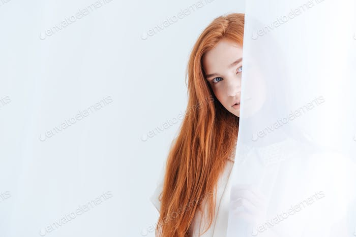 Woman peeking from curtain
