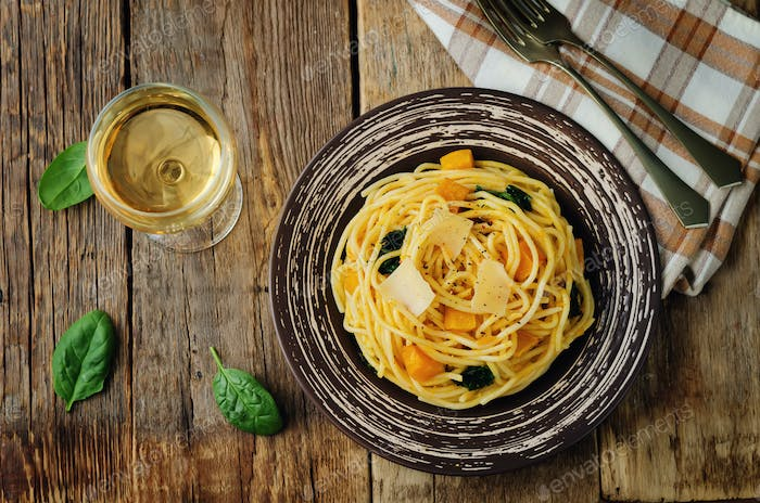 Pasta with pumpkin and spinach on a wood background