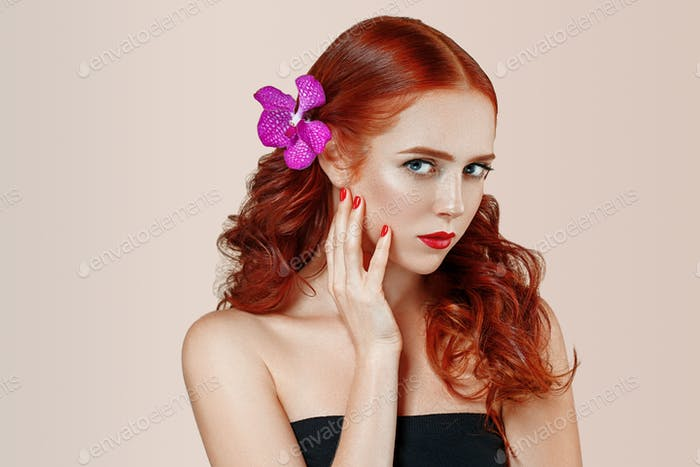 Beautiful woman portrait with flower in hair perfect make up manicure red lips and nails