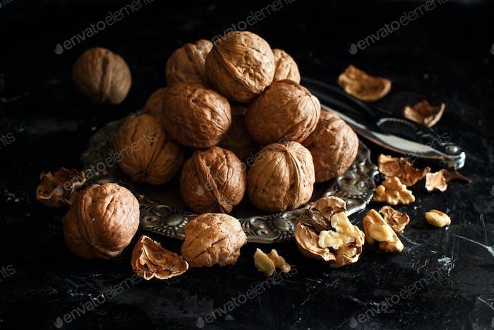 Fresh walnuts with a nutcracker on a dark background