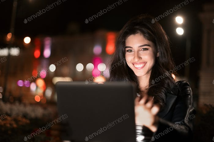 Happy girl making video-call on tablet in night city