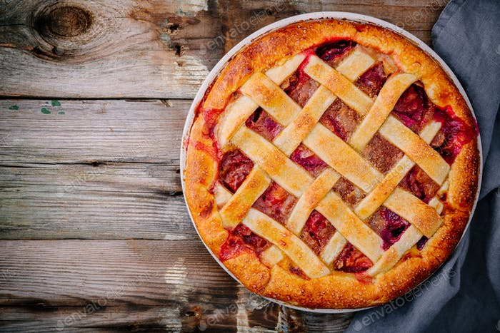 Homemade plum pie on rustic background