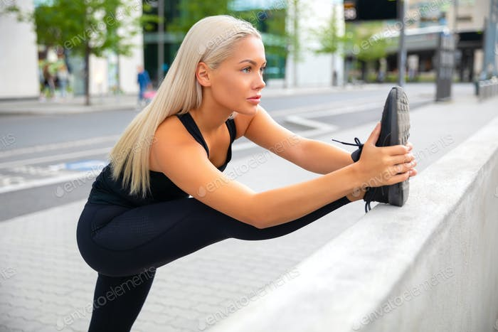Confident Female Athlete Stretching Leg On Railing At Sidewalk