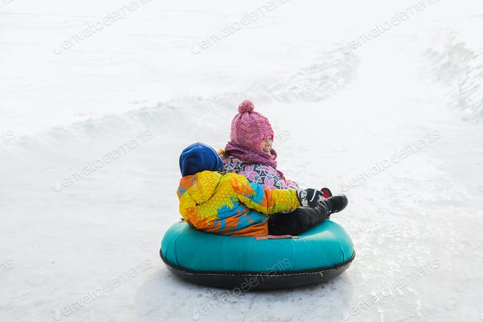 Little kids roll down the ice slide on tubing. Wintertime. Fun and games, outdoor activities concept