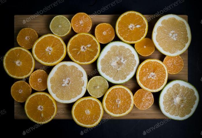Citrus fruits (orange, lemon, grapefruit, mandarin, lime) on the dark background