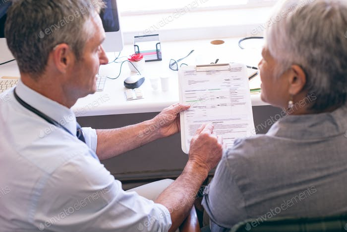 Male doctor showing medical report to the senior female patient at clinic at retirement home