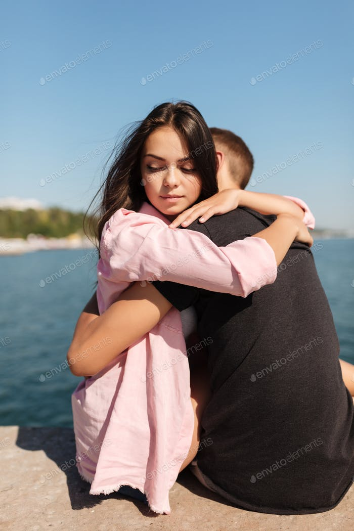 Young beautiful girl embracing cool boy while thoughtfully looking aside with sea view on background