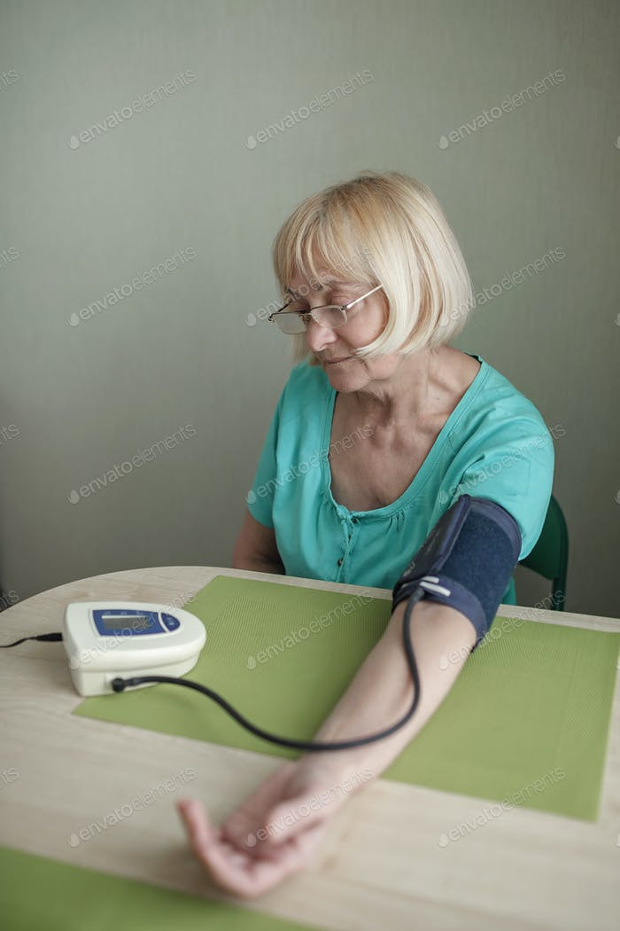 Senior adult using medical device and measuring blood pressure at home, health care and treatment
