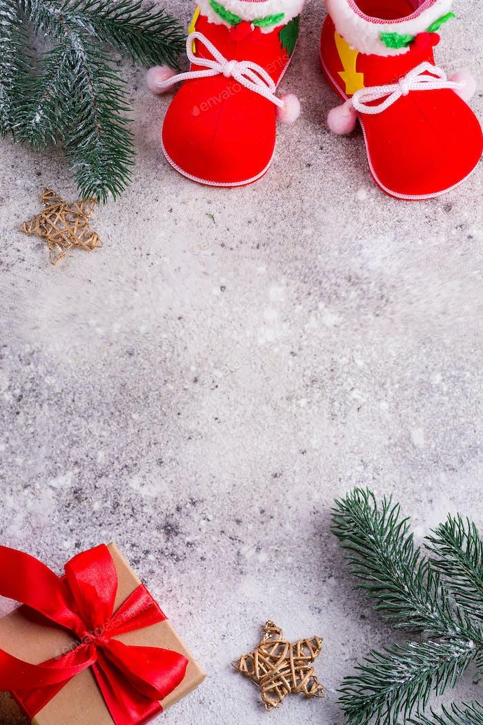Weihnachtsmannschuhe, Tannenzweige und Geschenkbox mit roten Bändern auf einem srone Hintergrund, Copz Space, oben