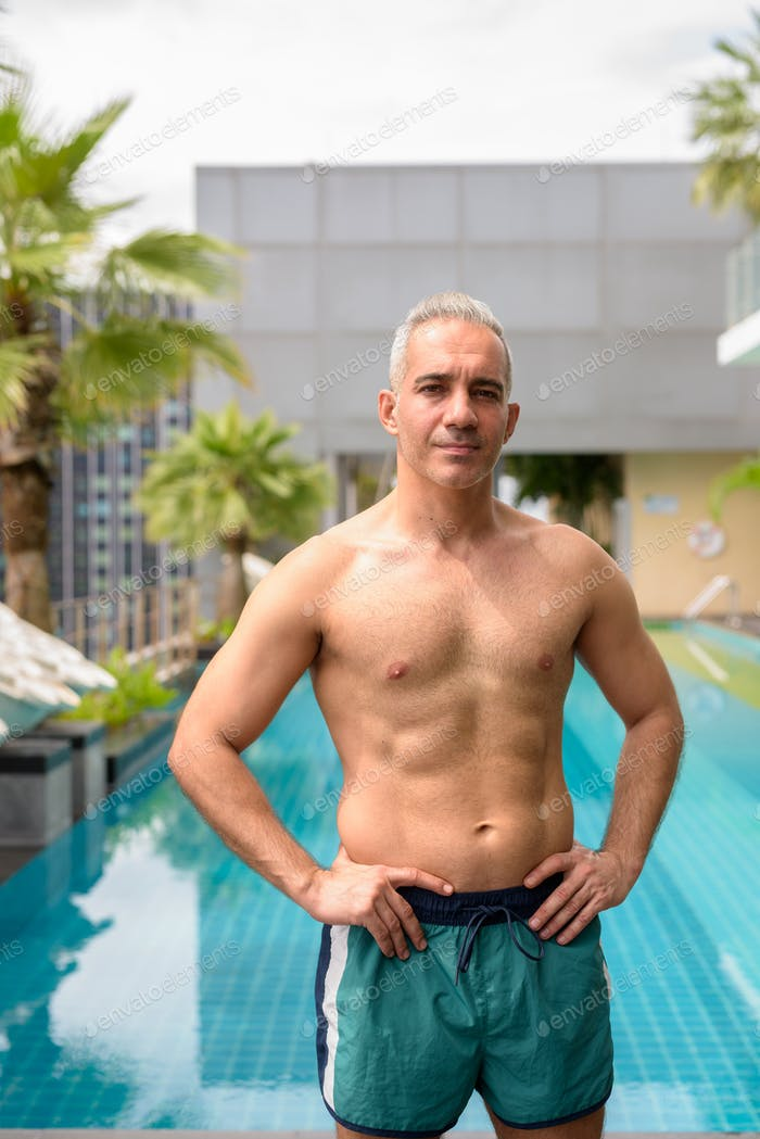 Mature handsome muscular Persian man shirtless and ready to swim