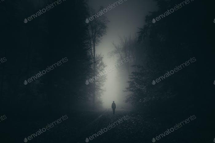 Ghost in dark haunted woods at night
