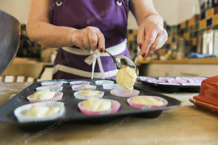 A woman at a kitchen table baking fairy cakes.