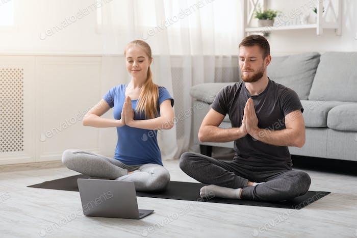 Junges tausendjähriges Paar praktiziert Yoga mit Lehrer online