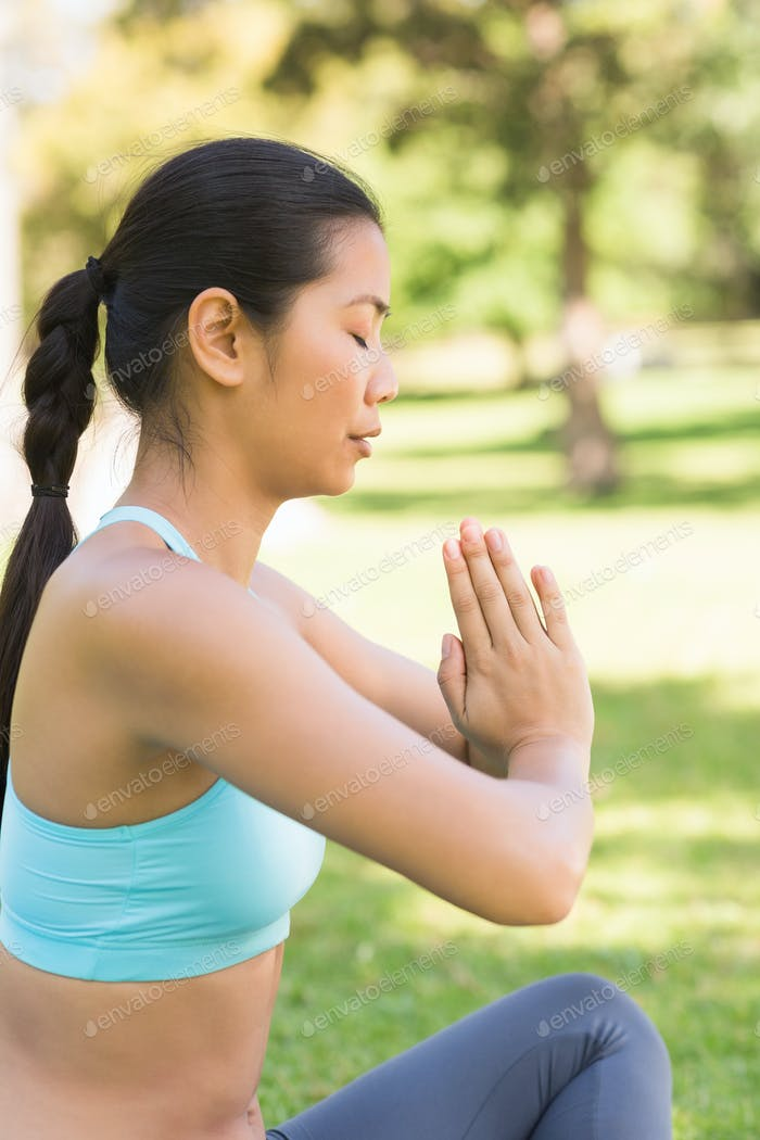 Side view of a sporty young woman in Namaste position with eyes closed at the park