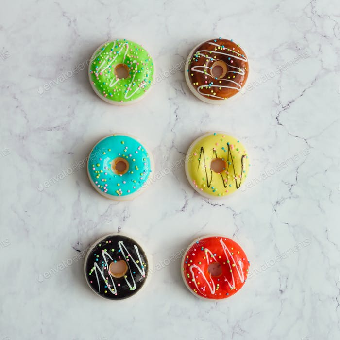 Creative arrangement of colorful donuts on marble background. Minimal food concept. Flat lay.