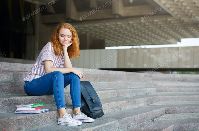 Young redhead student girl sitting on the stairs outdoors