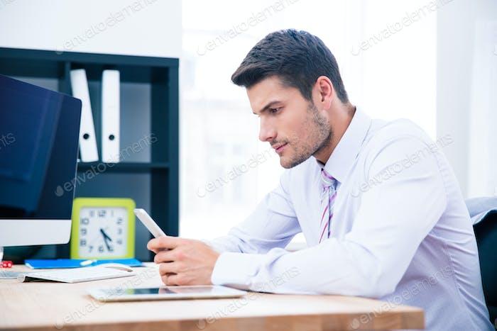 Hübscher Geschäftsmann sitzt am Tisch mit Smartphone