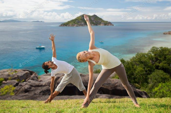 happy couple doing yoga outdoors