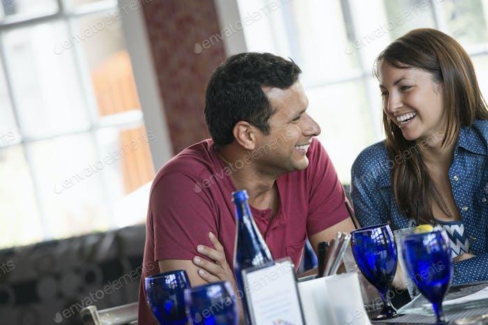 Un interior de café. Una pareja sentada en una mesa.