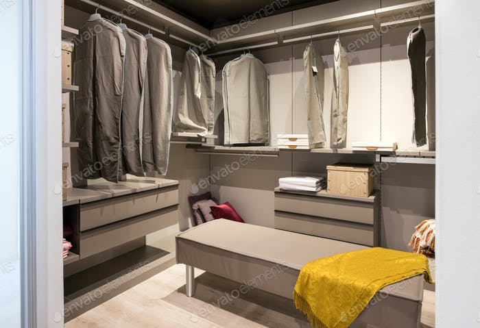 Interior of a walk in closet with hanging clothes