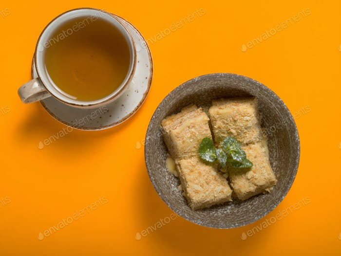 Sweet dessert with tea on a colored background