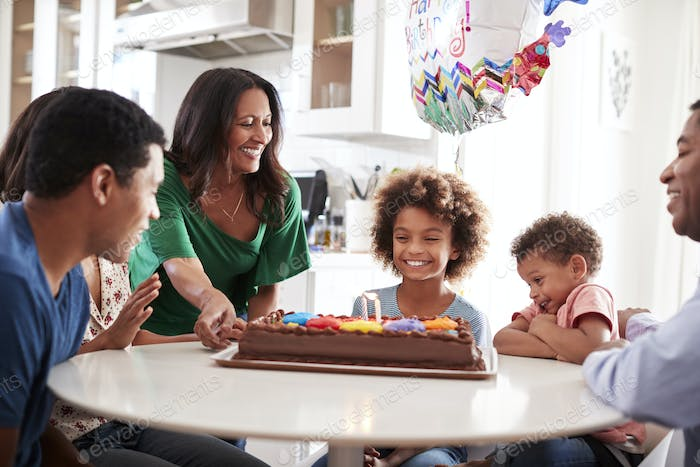Three generation family at the kitchen table celebrating daughter's birthday with a birthday cake