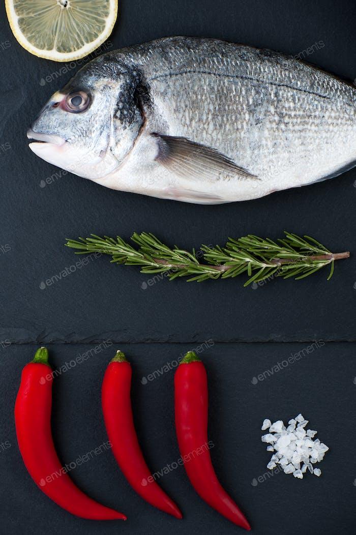 Fresh Dorado fish, lemon, chili pepper, rosemary and salt on a b