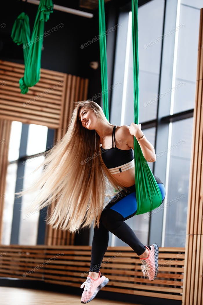 Young beautiful girl with long blond hair dressed in the sport clothes is doing fitness on the green
