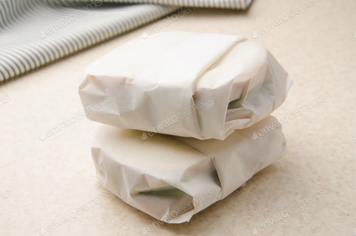 Two sandwiches wrapped in parchment paper on kitchen table