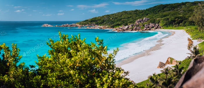 Panorama of epic Grand Anse Beach in La Digue island, Seychelles. White sand beach, big ocean waves