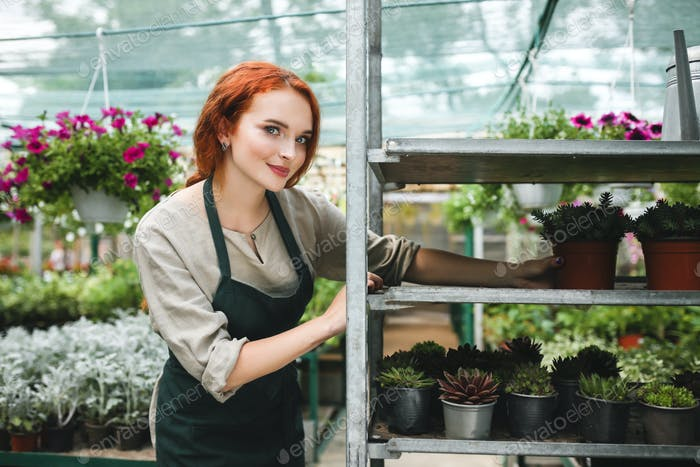 Pretty florist in apron working with flowers while dreamily looking in camera in big greenhouse