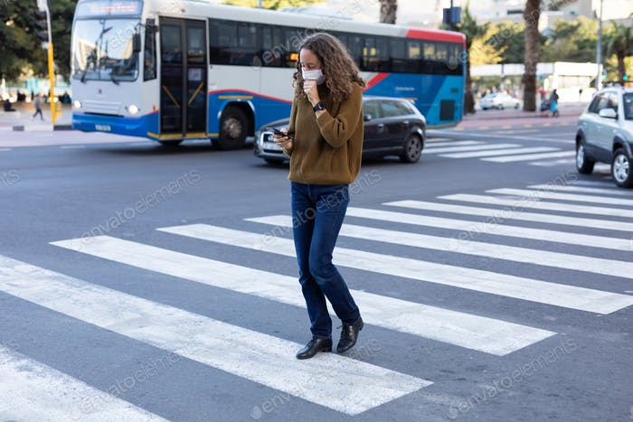 Caucasian woman wearing a protective mask and coughing out in the streets