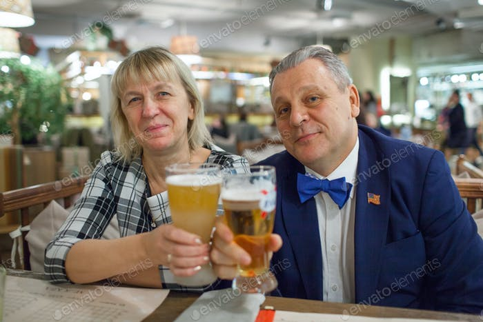 A portrait of a smiling middle aged couple with glasses of beer