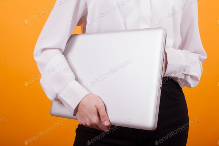 Portrait of young girl holding a laptop in studio over yellow background