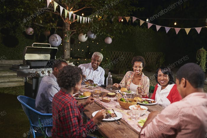 Adult black family enjoying dinner together in their garden