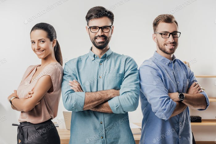 portrait of smiling business people with arms crossed standing at workplace in office
