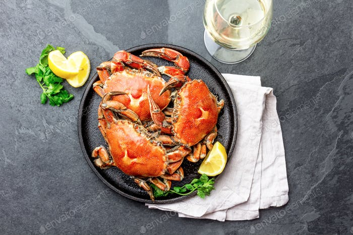 Cooked crabs on black plate served with white wine, black slate background, top view