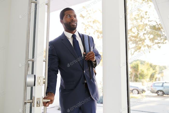 Businessman Wearing Suit Opening Door Returning Home From Work