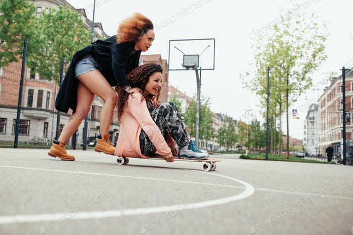 Young women having fun together with skateboard