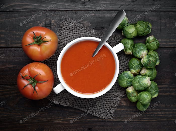 bowl of tomato sauce with tomatoes and other raw vegetables on rustic wood with natural light